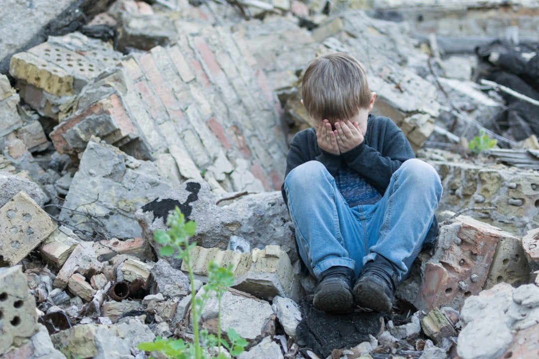 boy crying in remains of storm-destroyed home