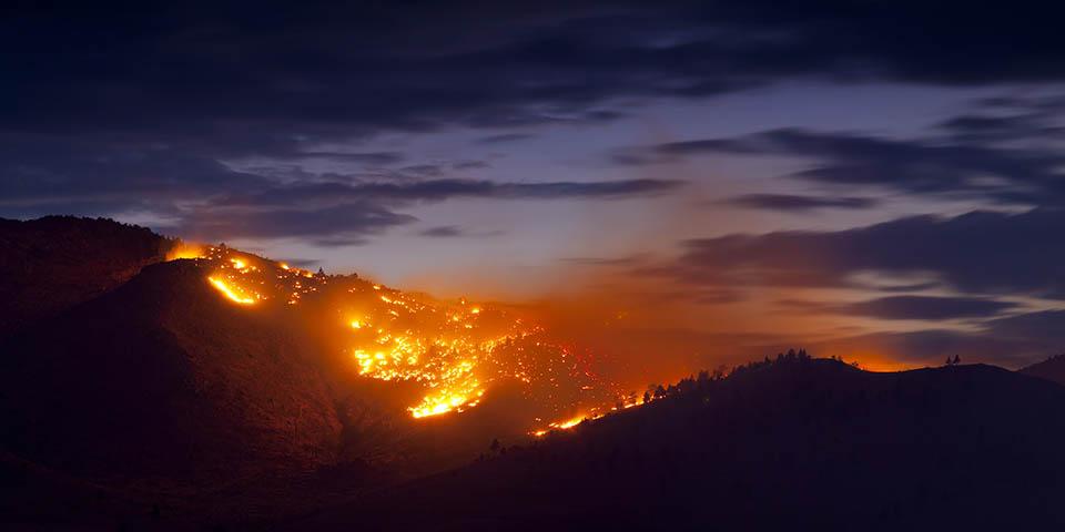 Wildfire burns against a dark blue sky