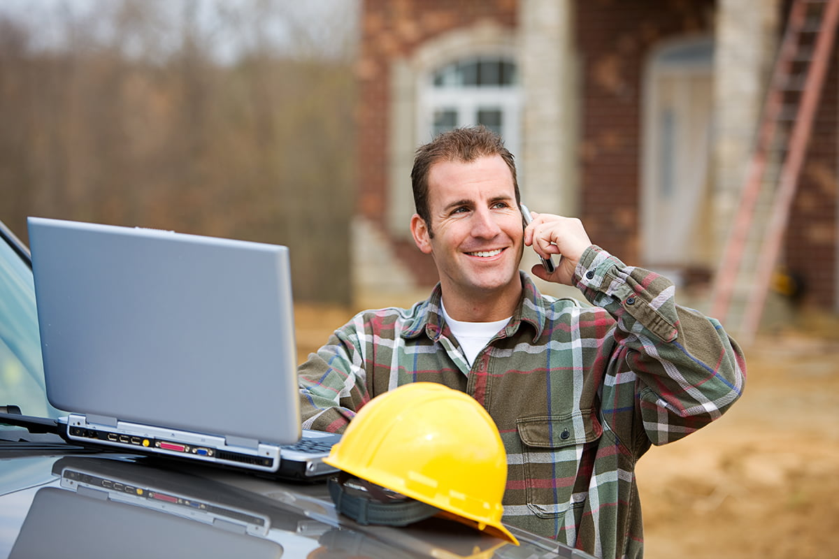 Man outside of a house with his laptop and hard hat on the hood of his truck. He's smiling while talking on a cell phone.