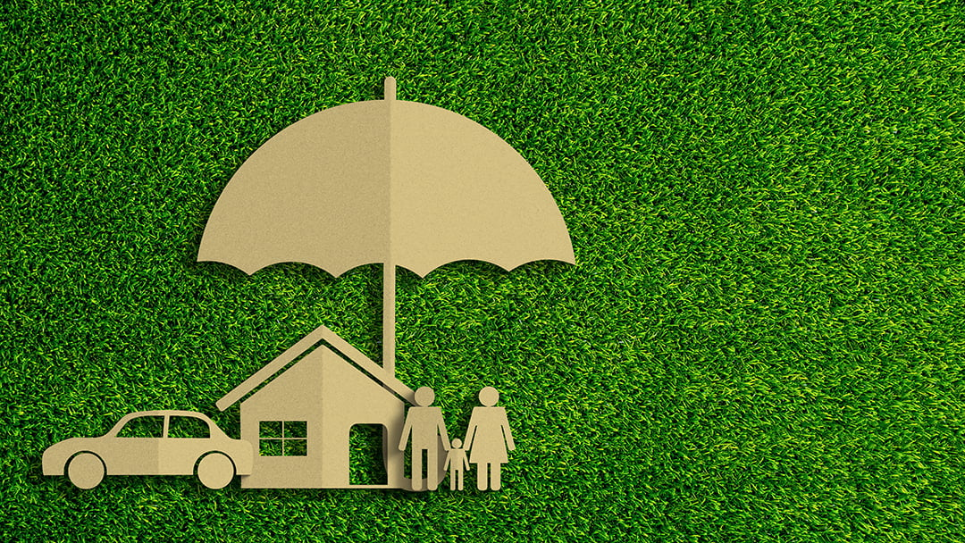 Kraft paper cutouts of a family, home, and car under a large umbrella set against a green grass background
