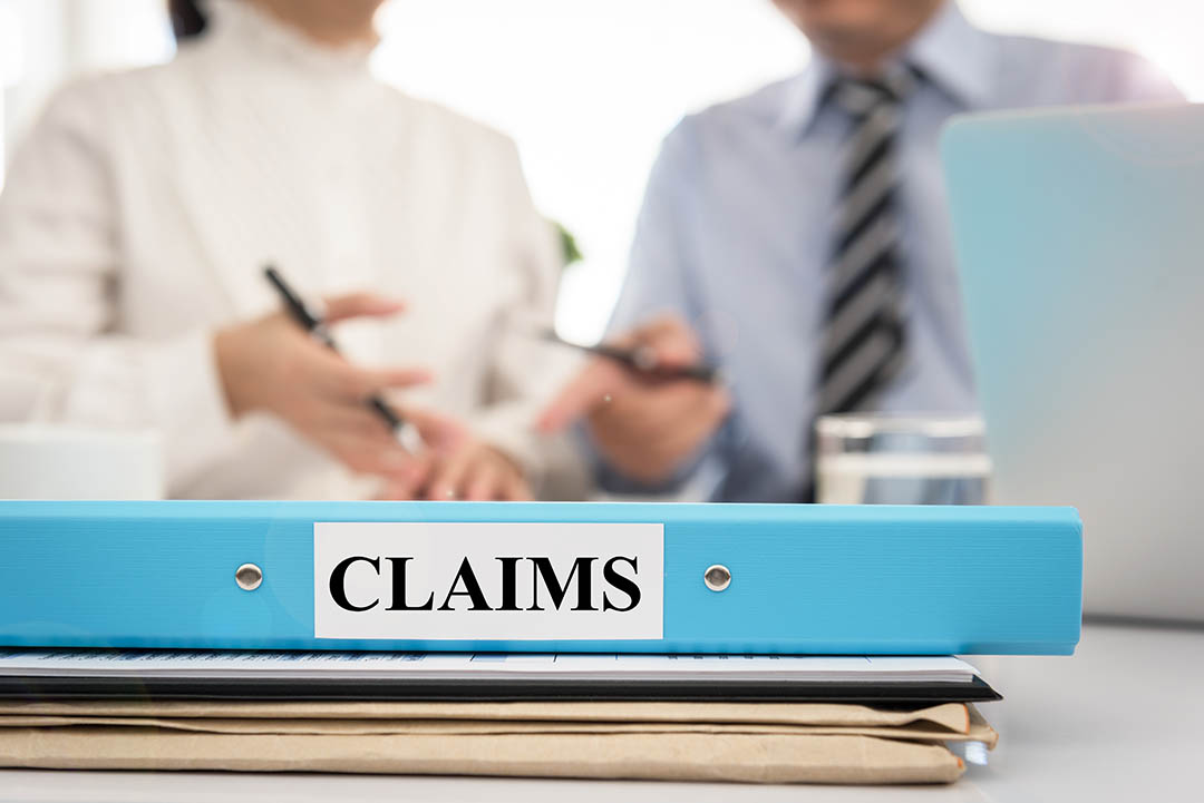 "Folder marked ""claims"" in the foreground with two professionals discussing a business matter in the background"