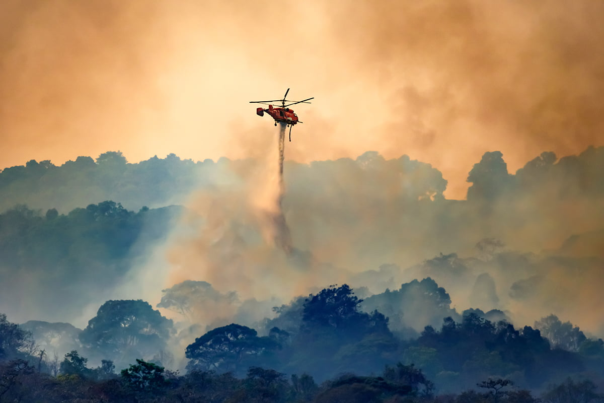 Helicopter drops water on burning wildfires